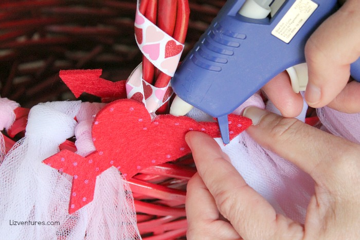 gluing embellishments onto Valentine's Day basket