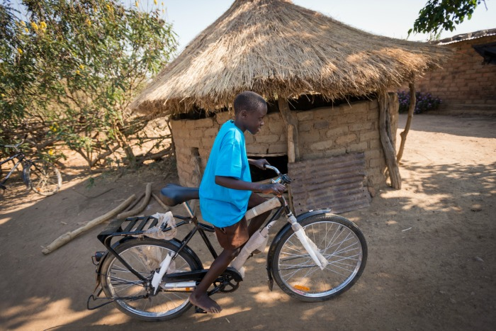 Sponsored child Aden Muzyamba, 11, rides a new World Bicycle Relief (WBR) bicycle at his home in Hamaundu, Zambia. Aden received the bicycle from his sponsor. He lives with his parents and is in Grade 4.