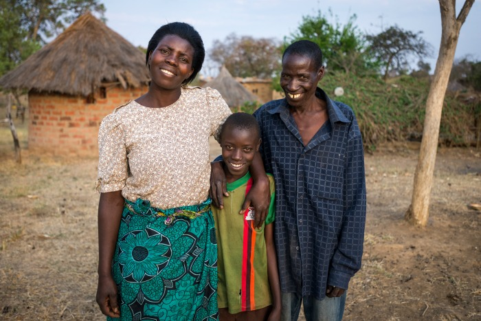 Sponsored child (center) Aden Muzyamba, 11, at his home in Hamaundu, Zambia with his mother Rosina Buumba and Father Sunday Buumba. He lives with his parents and is in Grade 4.