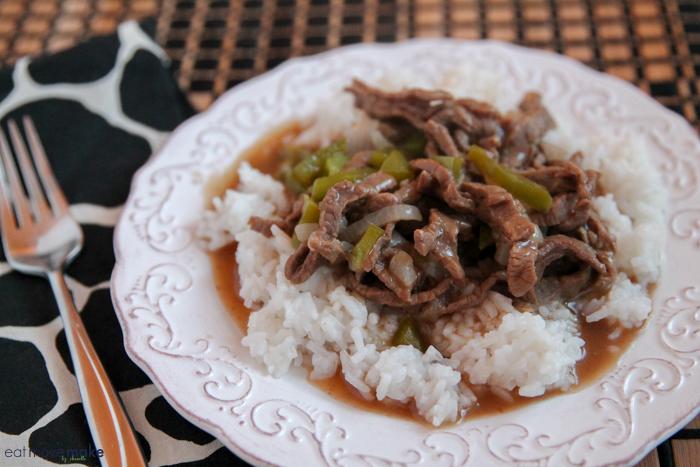 pepper steak served over rice on plate