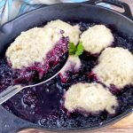 spoon holding blackberry dumplings